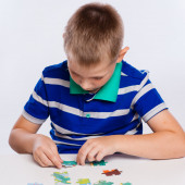 Cute little boy playing puzzles at the table — Stock Photo