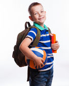 Happy schoolboy with backpack, ball and books isolated on white  — Stock Photo
