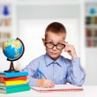 Cute schoolboy is writting isolated on a white background — Stock Photo #57577801