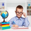 Cute schoolboy is writting isolated on a white background — Stock Photo #57577817
