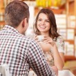 Seducing beautiful woman looking at her lover with coffee cup. Having romantic talk — Stock Photo #57578149