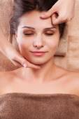 Eautiful young relaxed woman enjoy receiving face massage at spa saloon — Stock Photo