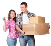 Moving, home and family concept - smiling couple holding cardboard boxes — Stock fotografie