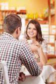Seducing beautiful woman looking at her lover with coffee cup. Having romantic talk — Stock Photo
