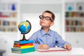 Cute schoolboy is writting isolated on a white background — Stock Photo