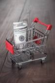 A hundred dollars in the shopping trolley — Stock Photo