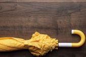 Folded yellow umbrella on the table — Zdjęcie stockowe