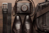 Brown shoes, belt, bag and film camera — Stock Photo