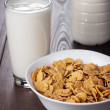 Glass of milk and bowl of cornflakes — Stock Photo #64882817