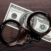 Handcuffs and one hundred dollars on wooden table — Stock Photo