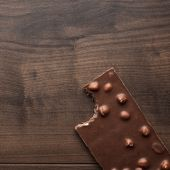 Nibbled chocolate bar with whole hazelnuts — Stock Photo
