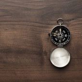 Compass on the brown wooden table — Stock Photo