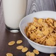 Glass of milk and bowl with cornflakes — Stock Photo #69110581