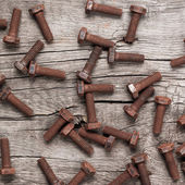 Rusty screw bolt on the wooden table — Stock Photo