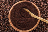 Coffee beans and wooden bowl full of ground coffee — Stock Photo