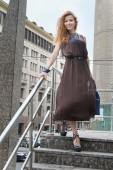 Beautiful woman standing on stairs — Stock Photo