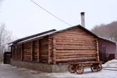 Log house with a cart — Stock Photo
