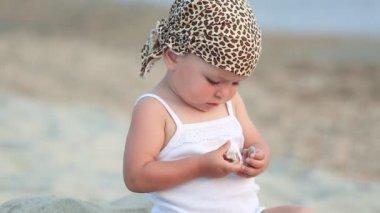 Baby flicka sitter och spelar på stranden — Stockvideo