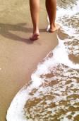 Femme qui marche sur la plage de sable — Photo