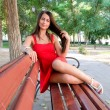 Girl sitting on park bench — Stock Photo #52476689
