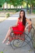 Flicka sitter på parkbänk — Stockfoto
