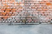 Red brick wall and a blacktop — Stock Photo