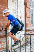 Child boy climbing over metal fence — Stock Photo