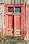 Aged red door with two glass windows on the top in old slum house in Astrakhan, Russia — Stock Photo