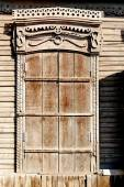Aged brown  closed shutters window of a old wooden slum house in Astrakhan, Russia — Stock Photo