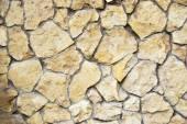 Yellow wild stone wall background — Stock Photo