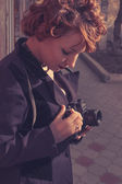 Vintage looking instagram style toned colors image of redhead women with camera in her hands — Stock Photo