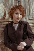 Retro portrait of red haired women in vintage coat agains obsolete wooden background — Stock Photo