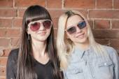 Two beautiful happy girls in trendy sunglasses on the urban background or red brick wall. Young hipster people. Outdoors portrait. — Stock Photo