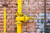 Yellow gas pipe and valve on red brick wall, copyspace — Stock Photo
