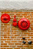 Red fire alarm sprinkler and hidrant in red brick wall — Stock Photo