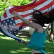 Beautiful patriotic  young woman with the American flag held in her hands dancing slowmo — Stock Video #73604397