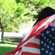 Patriotic  young woman with the American flag held in her hands dancing slowmo — Stock Video #73604587