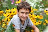 Boy against summer flower — Stock Photo
