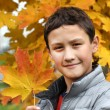 Boy holding maple leaf — Stock Photo #60132855