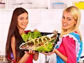 Women prepare fish in oven. — Stock Photo