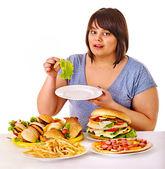 Woman choosing between fruit and hamburger. — Stock Photo