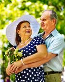 Happy old couple with flowers. — Stock Photo