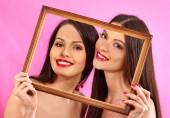 Lesbian women holding  art frame. — Stock Photo