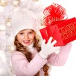 Girl in hat and mittens with gift box — Stock Photo #59878711