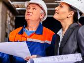 Business woman and man in builder helmets . — Stock Photo