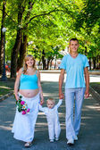 Pregnant woman with family outdoor. — Stock Photo