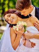 Bride and groom with flowers outdoor. — Stock Photo