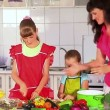 Mother and daughters cooking food at kitchen — Stock Video #73854999