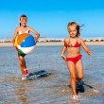 Children holding ball running on  beach. — Stock Photo #75129413