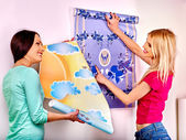 Women glues wallpapers at home. — Stock Photo